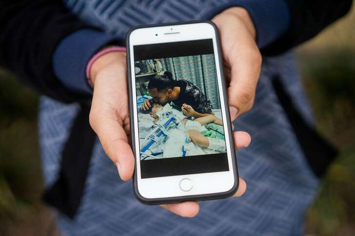Ali Hassan shows a photograph of him with his son in the ICU at UCSF Children's Hospital in Oakland, Calif. on Sunday, Dec. 16, 2018. Hassan's wife, who is in Yemen, is unable to see their dying son due to the travel ban from the seven majority Muslim countries.