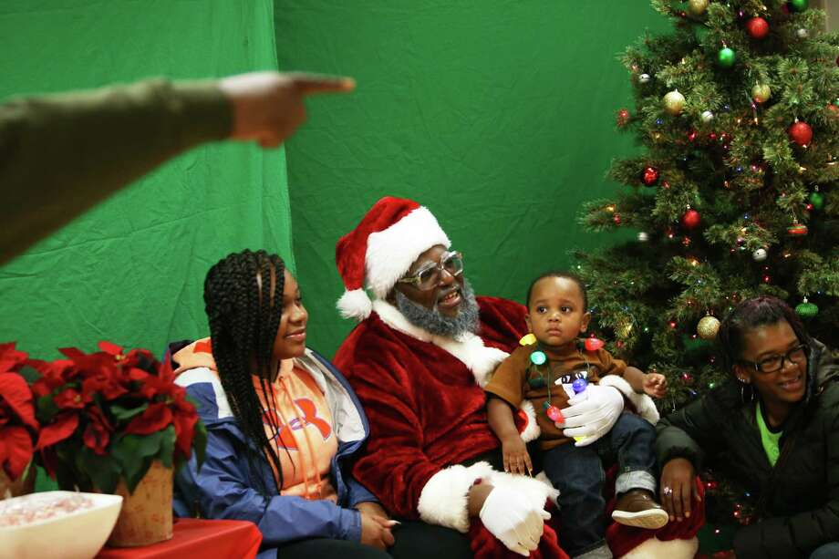 Chukundi Salisbury aka Black Santa sits with a family for a photo during a free event, hosted by the 100 Black Parents organization, at the Langston Hughes Performing Arts Center for kids to have their photos taken with Santa Claus. Photo: GENNA MARTIN, SEATTLEPI.COM / SEATTLEPI.COM