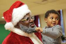 Kai Lawton, 3, gives Santa's beard a tug, Sunday, Dec. 16, 2018. The group 100 Black Parents hosted a free Black Santa event at the Langston Hughes Performing Arts Center for kids to have their photos taken with Santa Claus. Santa was played by Chukundi Salisbury.