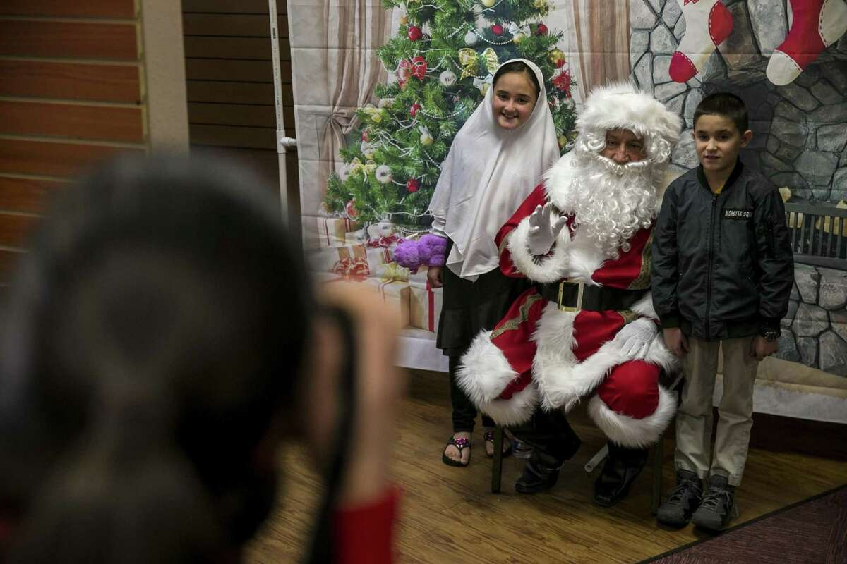 Diwa Mohammadkhan, 9, and her brother Monerahmad Mohammadkhan, 8, pose with Javier Roman dressed as Santa Claus during a Christmas party for refugee families and their children hosted by the Center for Refugee Services and Resurgent Church at the church, Dec. 15, 2018. Volunteers handed out donated gifts to children whose families have recently resettled in San Antonio.