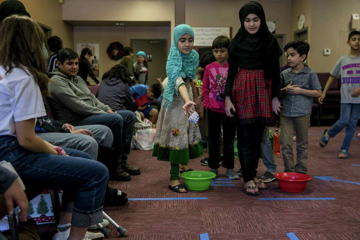 Saima Ahang, 9, plays a toss game with her sister Saheba Ahang, 11, during a Christmas party for refugee families and their children hosted by the Center for Refugee Services and Resurgent Church at the church, Dec. 15, 2018. Volunteers handed out donated gifts to children whose families have recently resettled in San Antonio.