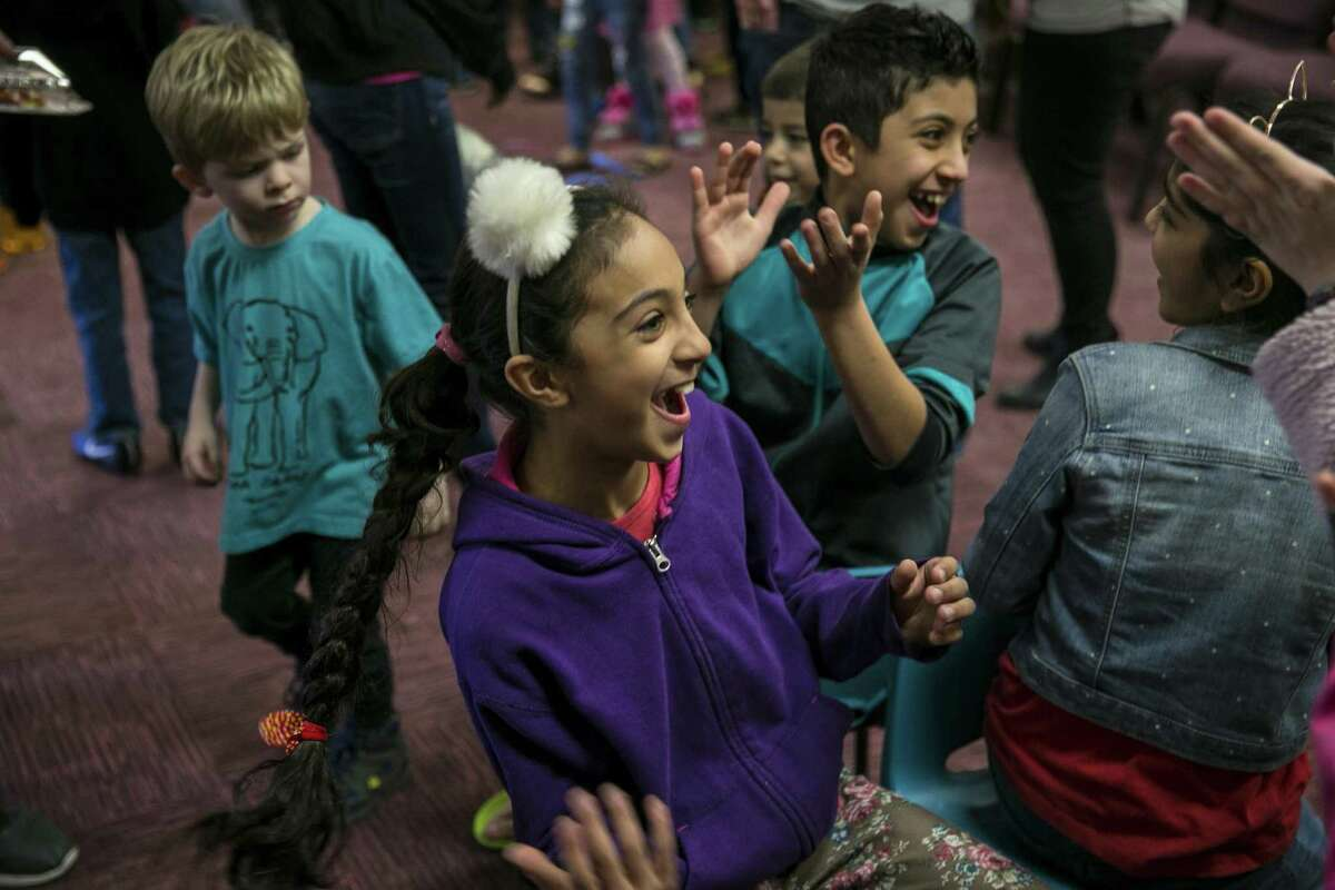 Children erupt in laughter while playing a game of musical chairs during a Christmas party for refugee families and their children hosted by the Center for Refugee Services and Resurgent Church at the church, Dec. 15, 2018. Volunteers handed out donated gifts to children whose families have recently resettled in San Antonio.
