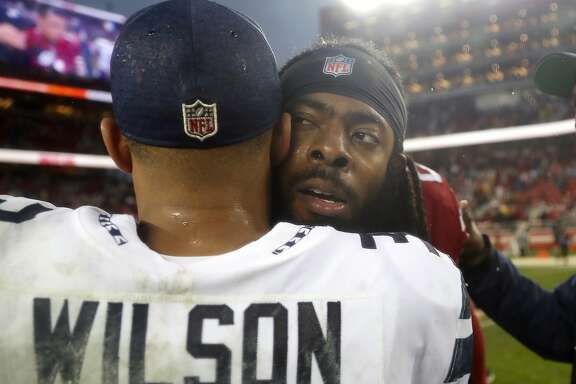 Seattle Seahawks quarterback Russell Wilson, left, hugs San Francisco 49ers defensive back Richard Sherman after an NFL football game in Santa Clara, Calif., Sunday, Dec. 16, 2018. (AP Photo/Tony Avelar)