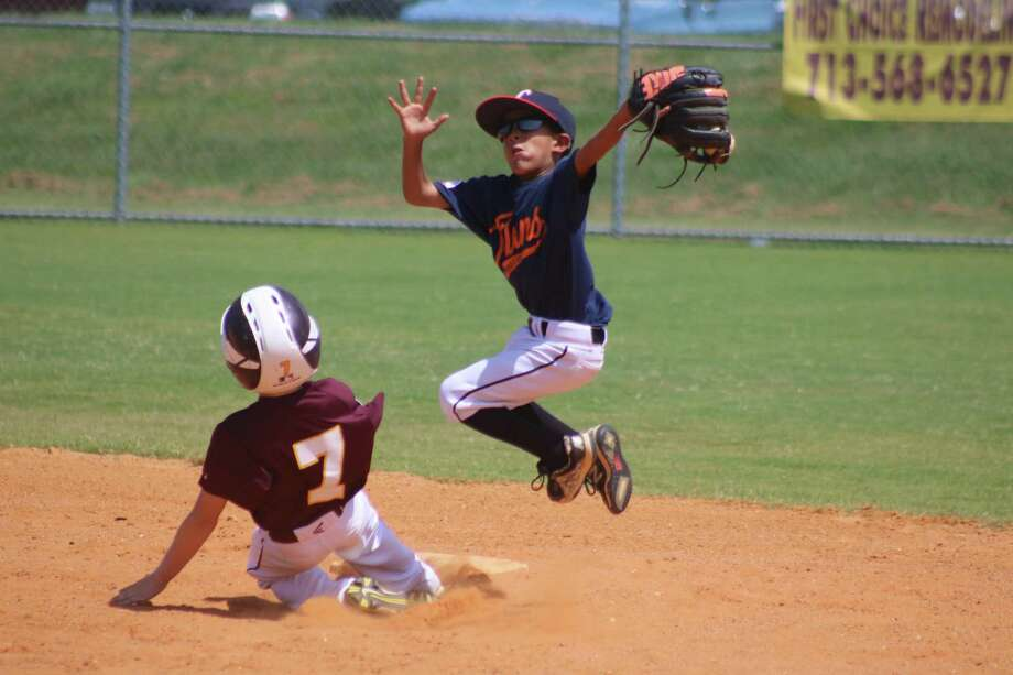 The arrival of the Holiday Baseball Camp at Spencerview Park Dec. 27-28 is a reminder that plays like this on the youth baseball diamond will be arriving again next spring and summer. Photo: Robert Avery