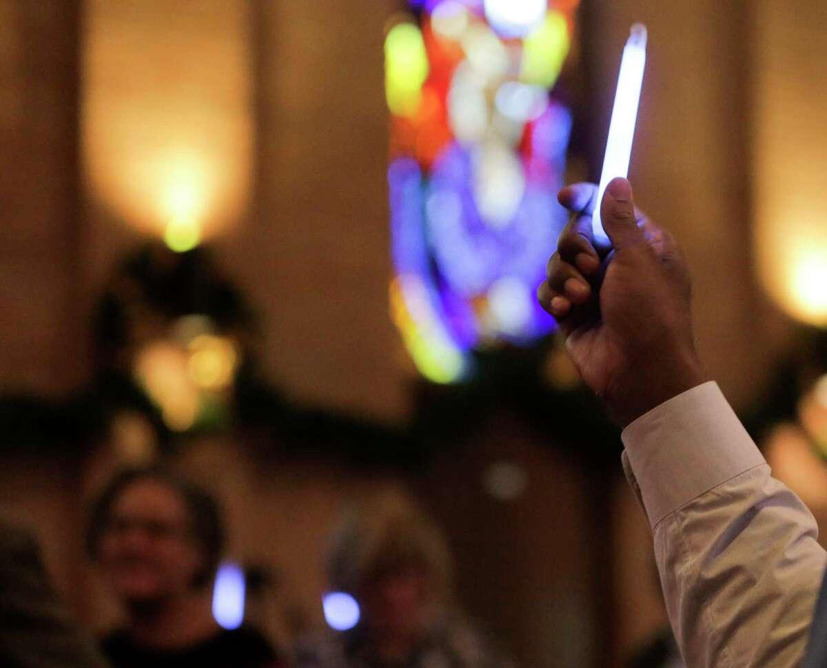 Rev. Ed Jones holds a glow stick during a a Gun Safety Vigil at his church, Trinity United Methodist Church in Houston on Sunday, Dec. 16, 2018.