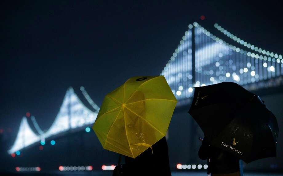 Ellen Pham, left, and Michelle Sheu, right, look out over the Bay Bridge Lights as rain falls along the Embarcadero in San Francisco, Calif., on Sunday, December 16, 2018. The regions is poised to see a week of rainy weather. Photo: Carlos Avila Gonzalez / The Chronicle