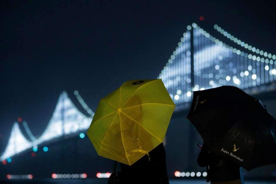 Ellen Pham, left, and Michelle Sheu, right, look out over the Bay Bridge Lights as rain falls along the Embarcadero in San Francisco, Calif., on Sunday, December 16, 2018. The regions is poised to see a week of rainy weather.