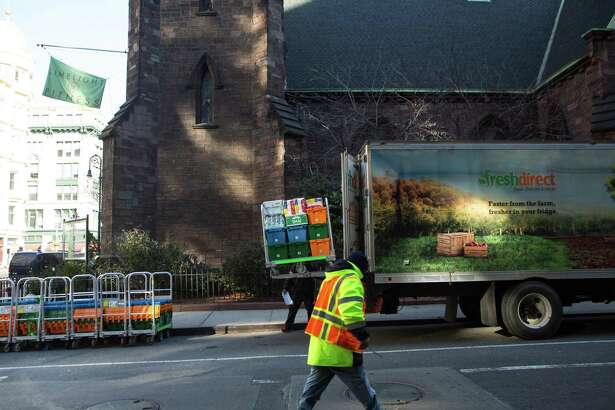 A worker unloads crates of groceries from a FreshDirect delivery truck in New York last week. FreshDirect is the leading online grocer in the most populous U.S. city, but it's losing market share as well-funded competitors such as Walmart and Amazon enter the arena.