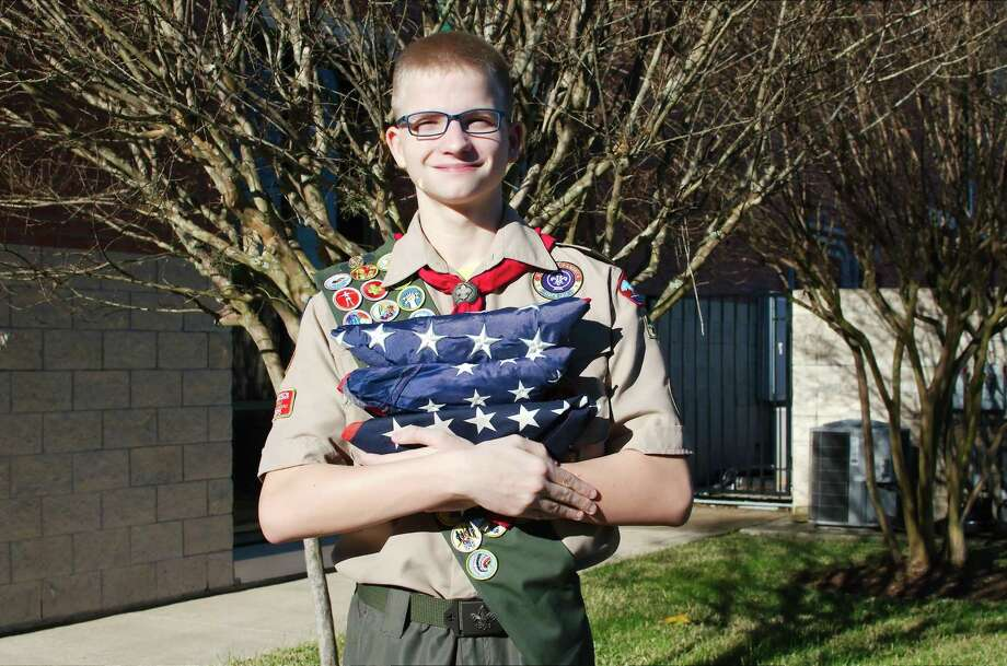 Friendswood Eagle Scout Daniel Morgan holds retired American flags and stands on the site behind Friendswood City Hall where he has raised money for his Eagle Scout project to construct a drop box where residents can leave worn American flags for his troop to retire. Photo: Kirk Sides / Staff Photographer / © 2018 Kirk Sides / Houston Chronicle