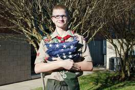 Friendswood Eagle Scout Daniel Morgan holds retired American flags and stands on the site behind Friendswood City Hall where he has raised money for his Eagle Scout project to construct a drop box where residents can leave worn American flags for his troop to retire.