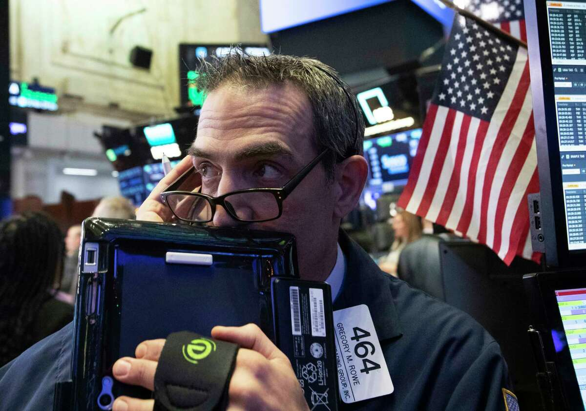 FILE- In this Dec. 12, 2018, file photo trader Gregory Rowe works at the New York Stock Exchange, Wednesday, Dec. 12, 2018, in New York. The U.S. stock market opens at 9:30 a.m. EST on Monday, Dec. 15.