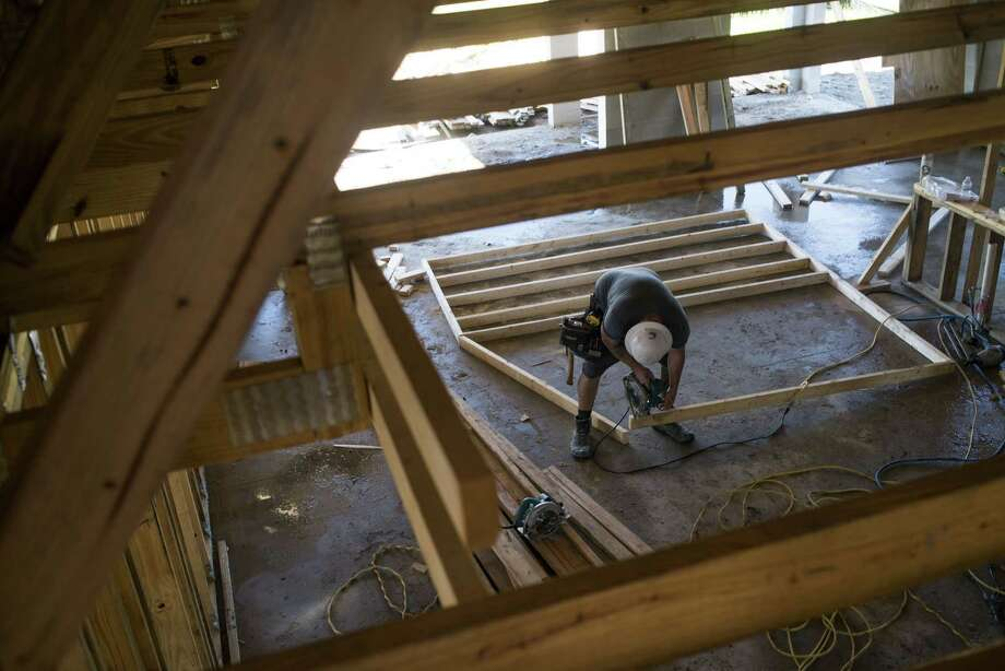 A worker saws a section of lumber inside a home under construction at the M/I Homes Inc. Bougainvillea Place housing development in Ellenton, Fla., on July 6, 2017. Photo: Bloomberg Photo By Ty Wright. / The Washington Post