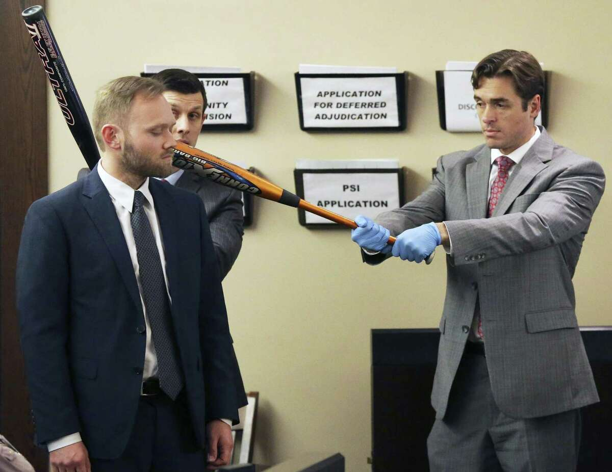 Prosecutors Matthew Ludowig (left) and Josh Somers demonstrate how they suggest that bats were used on a a victim as testimony is heard on February 28, 2018 in the trial of Gabriel Moreno, accused of killing Jose Luis Menchaca.
