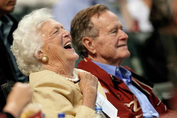 FILE - In this April 18, 2009, file photo, Barbara Bush laughs alongside former President George H.W. Bush, right, as they attend a baseball game in Houston. Barbara Bush, the snowy-haired first lady whose plainspoken manner and utter lack of pretense made her more popular at times than her husband, President George H.W. Bush, died Tuesday, April 17, 2018. She was 92.