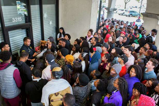 Houston Police Department officers try to disperse a crowd assembled at a Sprint store on Westpark near Buffalo Speedway who had come to the store hoping to get free tickets to a Lil Wayne concert, Monday, Dec. 17, 2018 in Houston. Store personnel remained locked inside and told police that they did not have any more tickets to give away.