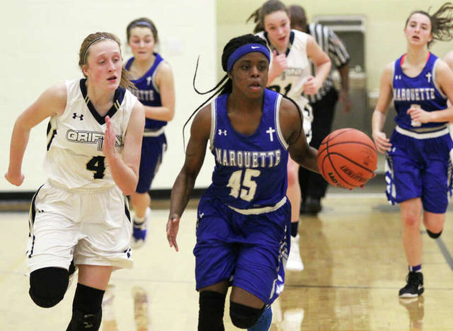 Marquette Catholic freshman Adrenna Snipes (45) breaks away to the basket while Father McGivney's Anna McKee (left) pursues the play in the Explorers victory Thursday in Glen Carbon. Snipes is averaging 16.7 points a game for the 8-4 Explorers. Photo: Greg Shashack / The Telegraph