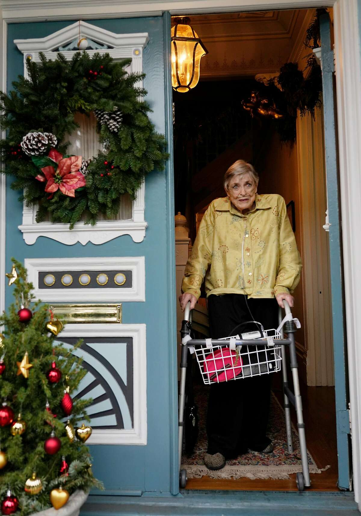 Catherine Sheehan Horsfall, who lives in one of the Painted Ladies, stands for a portrait in the doorway of her home on Tuesday, December 4, 2018 in San Francisco, Calif.