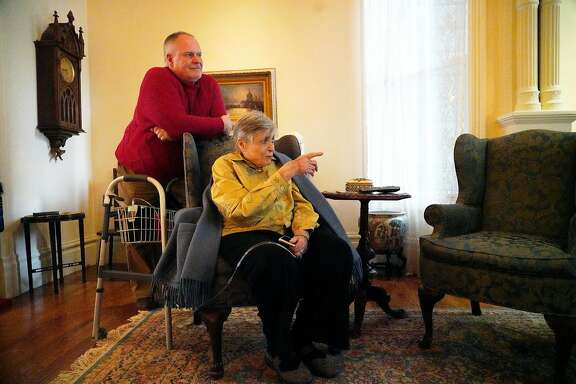 George Horsfall (l to r) stands behind his mother Catherine Sheehan Horsfall, who lives in one of the Painted Ladies,  as she sits a chair at her home on Tuesday, December 4,  2018 in San Francisco, Calif.