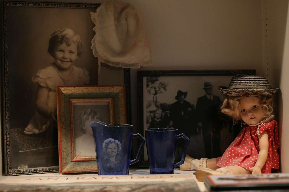 Childhood photos of Catherine Sheehan Horsfall, who lives in one of the Painted Ladies, are displayed in a cabinet of family memorabilia next to a Shirley Temple doll and cups on Tuesday, December 4, 2018 in San Francisco, Calif.