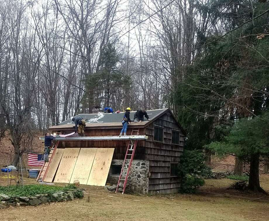 Students from Henry Abbott Technical High School repaired the roof of a disabled Vietnam veteran, helping her stay in her Danbury home. Photo: Contributed Photo / Contributed / The News-Times Contributed