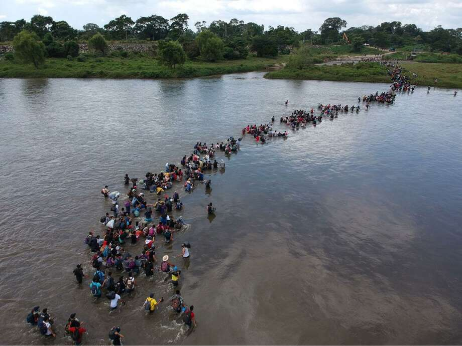 Aerial view of Salvadorean migrants heading in a caravan to the U.S., crossing the Suchiate River to Mexico, from Ciudad Tecun Uman, Guatemala, on Nov. 2. Demonizing such refugees as become a norm in some quarters in the U.S. Photo: CARLOS ALONZO /AFP /Getty Images / AFP or licensors