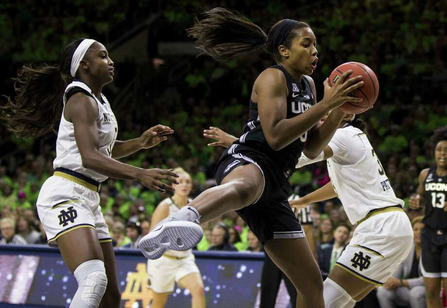 UConn's Megan Walker, center, grabs a rebound between Notre Dame's Jackie Young, left, and Danielle Patterson on Dec. 2, in South Bend, Ind. Photo: Robert Franklin / Associated Press / FR17139 AP