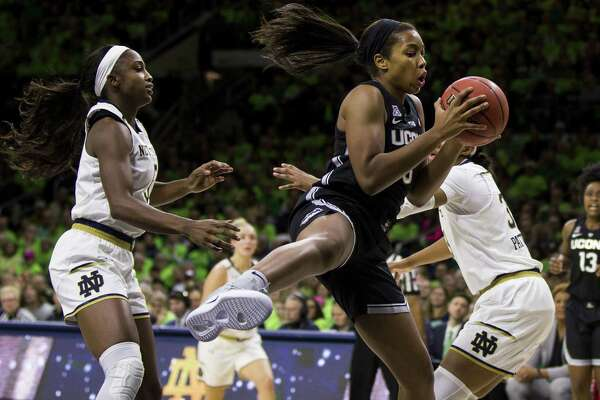 UConn's Megan Walker, center, grabs a rebound between Notre Dame's Jackie Young, left, and Danielle Patterson on Dec. 2, in South Bend, Ind.