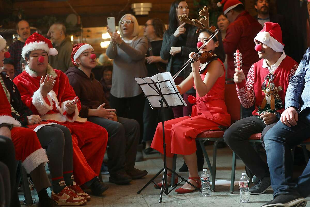 Para educator Sunghye Lee (middle, right) plays the violin next to Josue Colindres (right) at the singalong concert at Arc on Monday, Dec. 17, 2018, in San Francisco, Calif. Special education high school and above SFUSD students present holiday singalong concert at Arc.