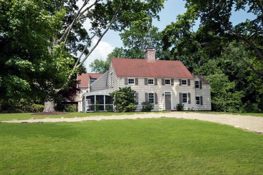 The cream-colored colonial house at 4 Christmas Lake Lane sits on a two-acre level, corner lot in a very convenient location.