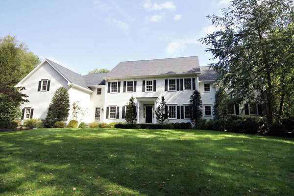 The white colonial house with black shutters at 110 Old Hickory Road in the Greenfield Hill neighborhood is close to the shops, major roads, and train stations in Fairfield and Westport.