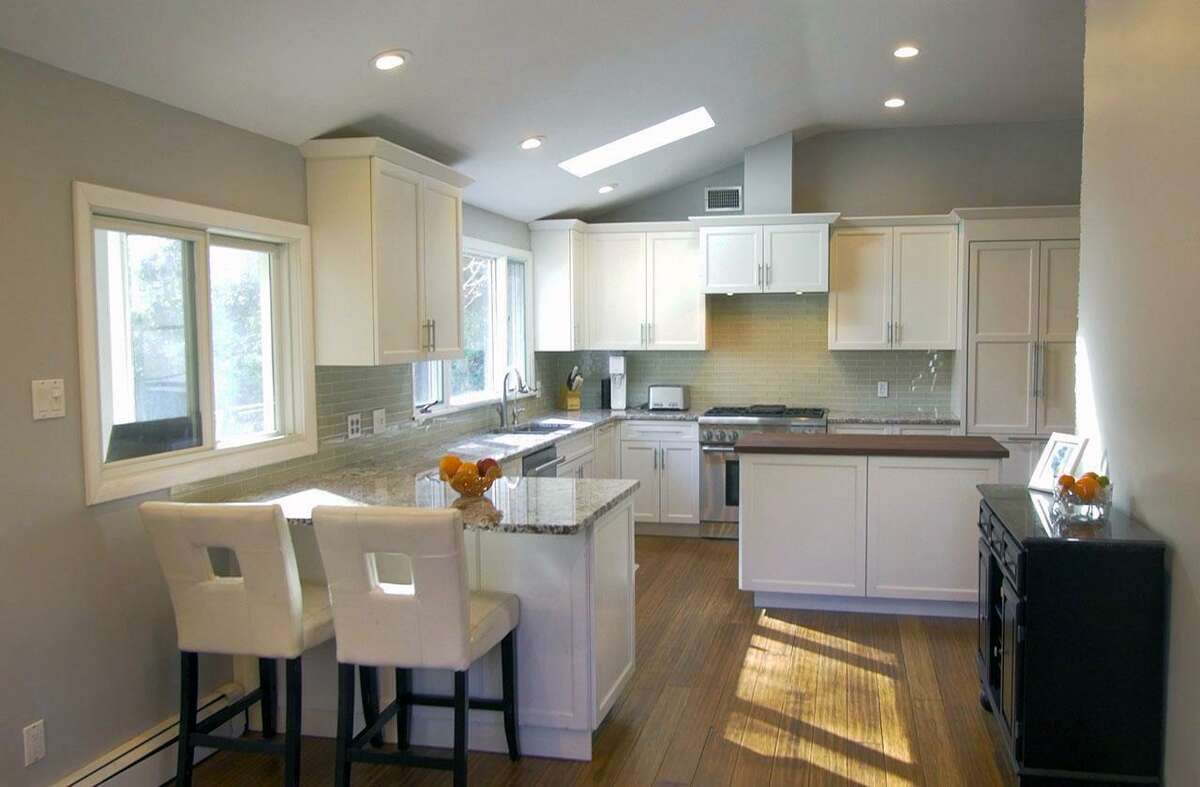 The newly remodeled kitchen features granite counters, double stainless sinks, a skylight, center island, a separate breakfast bar for two and high-end appliances including a Thermador Professional four-burner range.