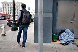 A pedestrian walks past a person humbled in a doorway on 5th St. in San Francisco, California, on Monday, December 17, 2018.