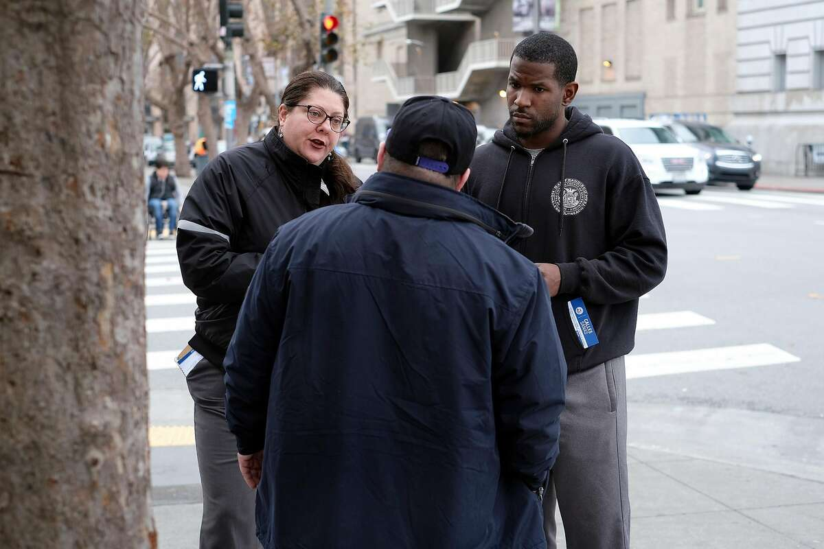 Homeless Outreach Team members Mecca Cannariato (left) and Cedric Bowser try to help Tim Riessen enter a Navigation Center in San Francisco in December 2018. A new national homeless plan rewrites the guidelines on
