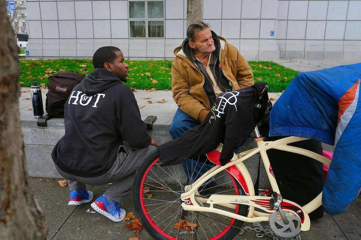 HOT team member Cedric Bowser, left, talks with homeless man Ron Quasebarth as he tries to set him up to enter a navigation center, in San Francisco, California, on Monday, December 17, 2018.