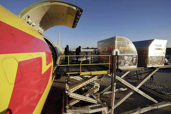 Worldwide Freight Services employees unload cargo containers from a DHL cargo plane at the DHL facility located on the west side cargo ramp of IAH Tuesday, Dec. 11, 2018 in Humble, TX.