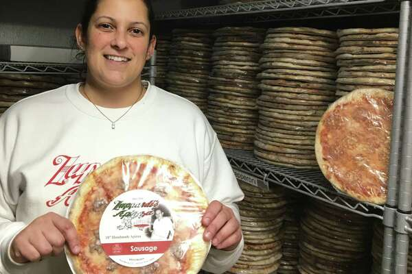 Cheri Zuppardi, daughter of Zuppardi's Apizza co-owner, is in charge of Zuppardi's new USDA-certified kitchen for wholesale orders to get Zuppardi's into stores. Here she poses in a walk-in freezer with thousands of Zuppardi's pies ready for shipment.