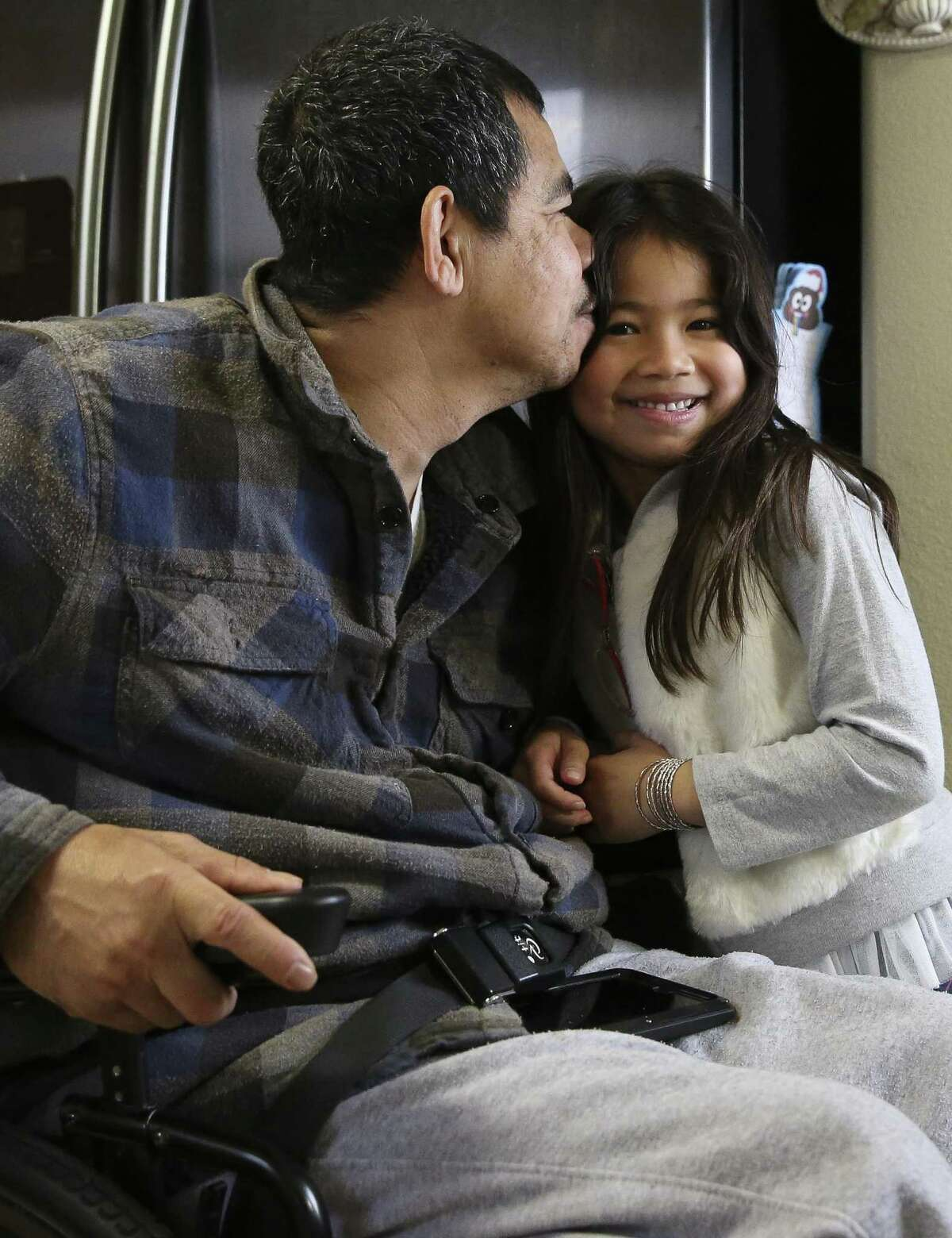 Khanh Hung Le, 47, kisses his daughter, Tonya, 7, when she comes home after school. Le has raised his daughter since she was 7 months old after he separated from his ex-wife.