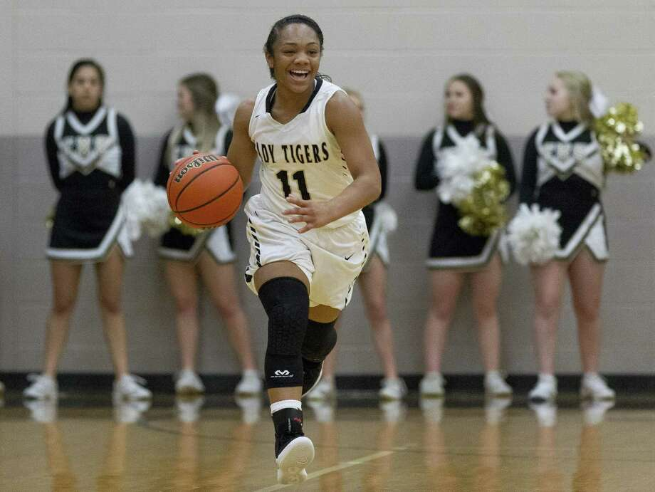 Conroe guard Kennedy Powell (11) smiles as she brings the ball up court during the second quarter of a District 15-6A high school girls basketball game against The Woodlands on Monday night. Photo: Jason Fochtman, Houston Chronicle / Staff Photographer / © 2018 Houston Chronicle