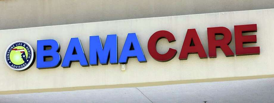 "File- This May 11, 2017, file photo shows an Obamacare sign being displayed on the storefront of an insurance agency in Hialeah, Fla. A conservative federal judge in Texas on Friday, Dec. 14, 2018, ruled the Affordable Care Act ""invalid"" on the eve of the sign-up deadline for next year. But with appeals certain, even the Trump White House said the law will remain in place for now. In a 55-page opinion, U.S. District Judge Reed O'Connor ruled Friday that last year's tax cut bill knocked the constitutional foundation from under ""Obamacare"" by eliminating a penalty for not having coverage. The rest of the law cannot be separated from that provision and is therefore invalid, he wrote. (AP Photo/Alan Diaz, File) Photo: Alan Diaz / Copyright 2017 The Associated Press. All rights reserved."