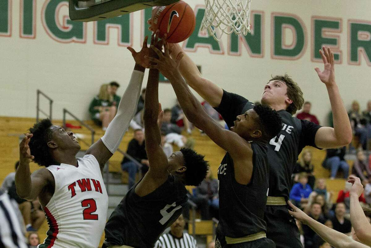 Conroe and The Woodlands players battle for a rebound during the fourth quarter of a District 15-6A high school boys basketball game at The Woodlands High School, Monday, Dec. 17, 2018, in The Woodlands.