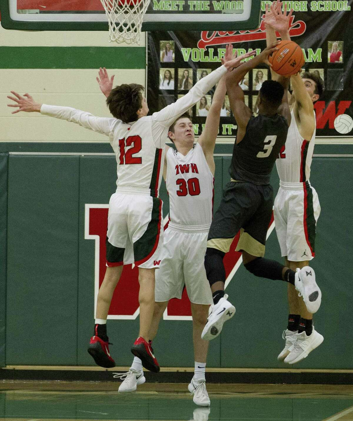 The Woodlands point guard Charlie Zorn (12), small forward Patrick Oed (30) and small forward Caleb Smith (22) contest a shot by Conroe guard Michael Phoenix (3) during the fourth quarter of a District 15-6A high school boys basketball game at The Woodlands High School, Monday, Dec. 17, 2018, in The Woodlands.