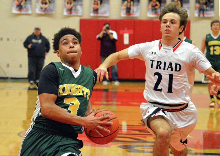 Metro-East Lutheran senior Jason Williams, left, drives to the basket after a steal during the third quarter of Monday's game at Triad.