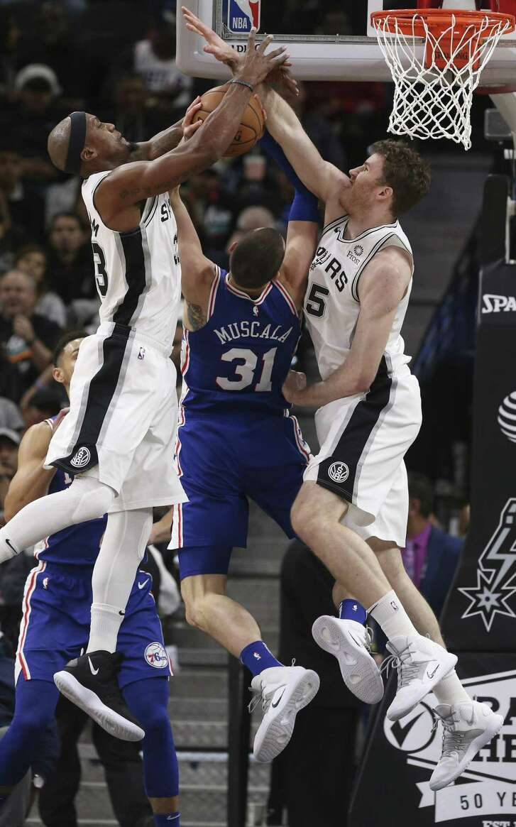 San Antonio Spurs' Dante Cunningham, left, and Jakob Poeltl ties up and block Philadelphia 76ers' Mike Muscala during the first half at the AT&T Center, Monday, Dec. 17, 2018.