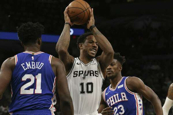 San Antonio Spurs?' DeMar DeRozan passes the ball under pressure from Philadelphia 76ers?' Joel Embiid and Jimmy Butler during the first half at the AT&T Center, Monday, Dec. 17, 2018.