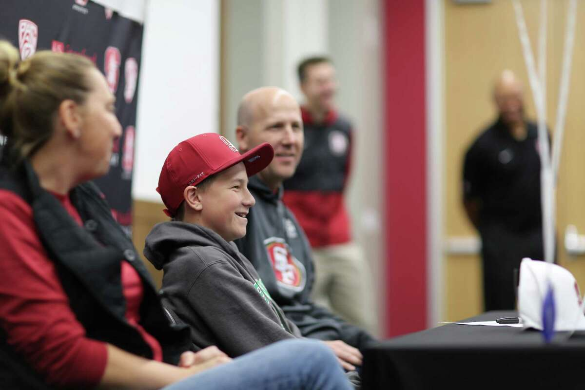 Cole Baker, 13, of San Mateo, flanked by parents Elisa and Jim Baker signed a ceremonial letter-of-intent to play for the Cardinal. Baker was diagnosed with neuroblastoma at age 5.