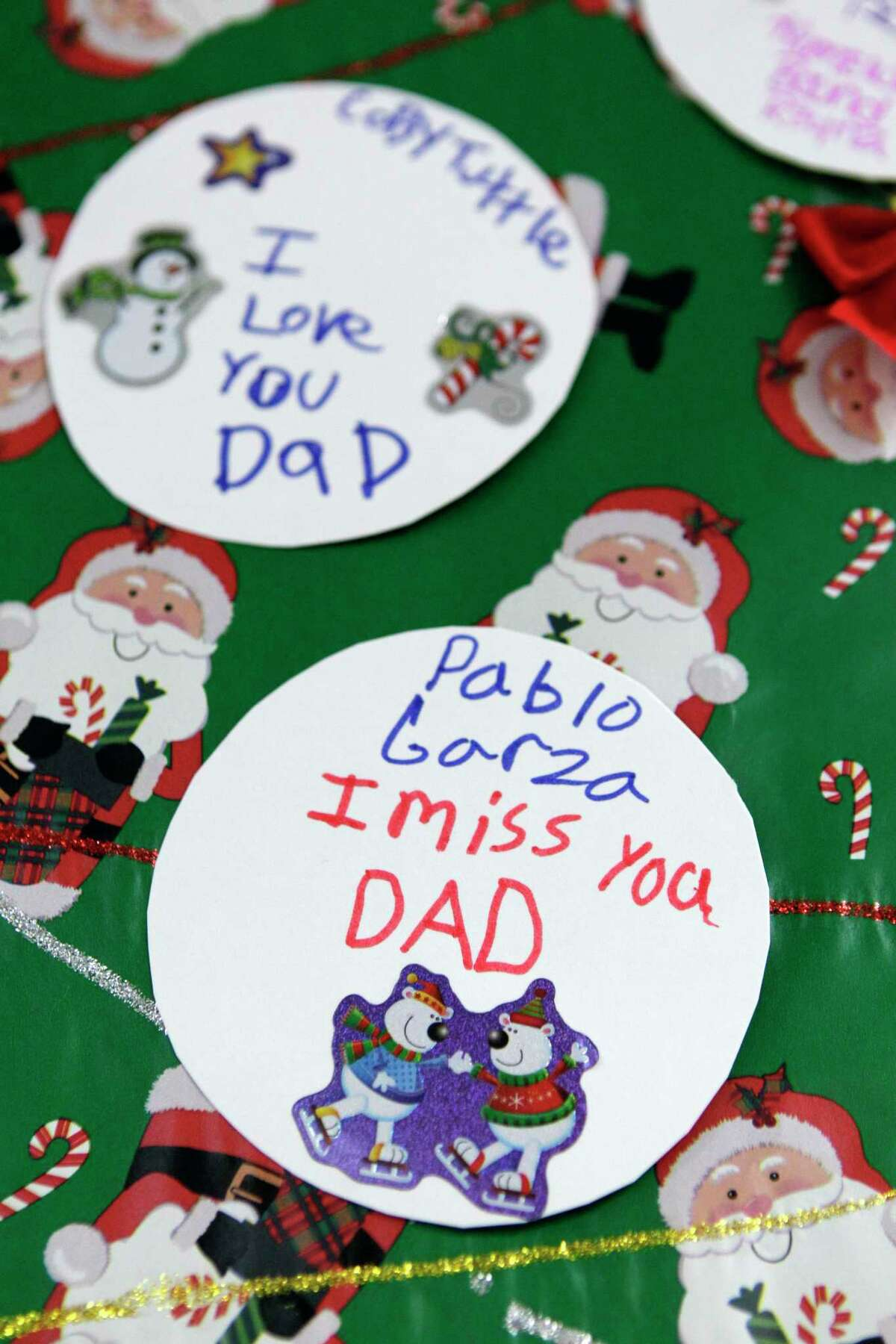 Children left messages for their incarcerated dads on a paper tree during the Angel Tree event at the Texas Department of Criminal Justice Carol Vance Unit Saturday, Dec. 7, 2013, in Richmond. The inmates are part of InnerChange Freedom Initiative, a faith based pre-release program, at the TDCJ Carol Vance Unit.