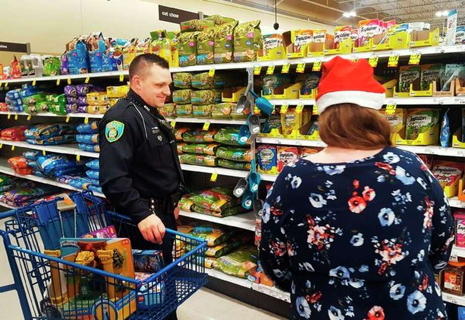 Midland Police Officer Eddie Hinson participates in the annual Shop with a Hero event on Tuesday at Meijer in Midland. During the annual program, which is a partnership between the store and The Salvation Army, the heroes were tasked with helping the children spend $100 gift cards, donated by Meijer, for Christmas. (Photo provided/Kelly Dame)