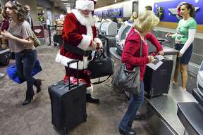 FILE - In this Wednesday, 21, 2011, file photo, holiday travelers, including Donald Occimio of Mesa, Ariz., dressed as Santa Claus, and his wife Diane check in with customer service agent Angelee Arciniega, right, for their Southwest Airlines flight at the Terminal 4 ticketing area at Sky Harbor International Airport, in Phoenix. The 2012 Christmas travel season could be the busiest in six years, with AAA predicting that 93.3 million Americans will hit the road. That's 1.6 percent more than last year and just 400,000 people shy of the 2006 record. (AP Photo/The Arizona Republic, Tom Tingle) MARICOPA COUNTY OUT; MAGS OUT; NO SALES