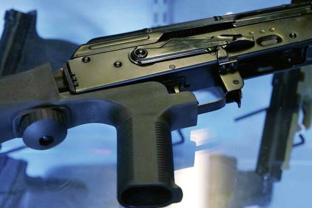 """FILE - In this Oct. 4, 2017 file photo, a little-known device called a """"bump stock"""" is attached to a semi-automatic rifle at the Gun Vault store and shooting range in South Jordan, Utah. The Trump administration is moving to officially ban bump stocks, which allow semi-automatic weapons to fire rapidly like automatic firearms. A senior Justice Department official said Tuesday bump stocks will be banned under the federal law that prohibits machine guns. It will take effect in late March."""