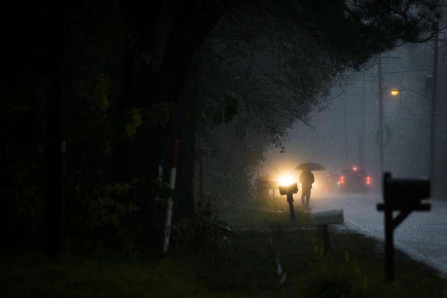 A pedestrian walks under the rain on Simmons Drive in Tamina. Photo: Marie D. De Jesús/Staff Photographer